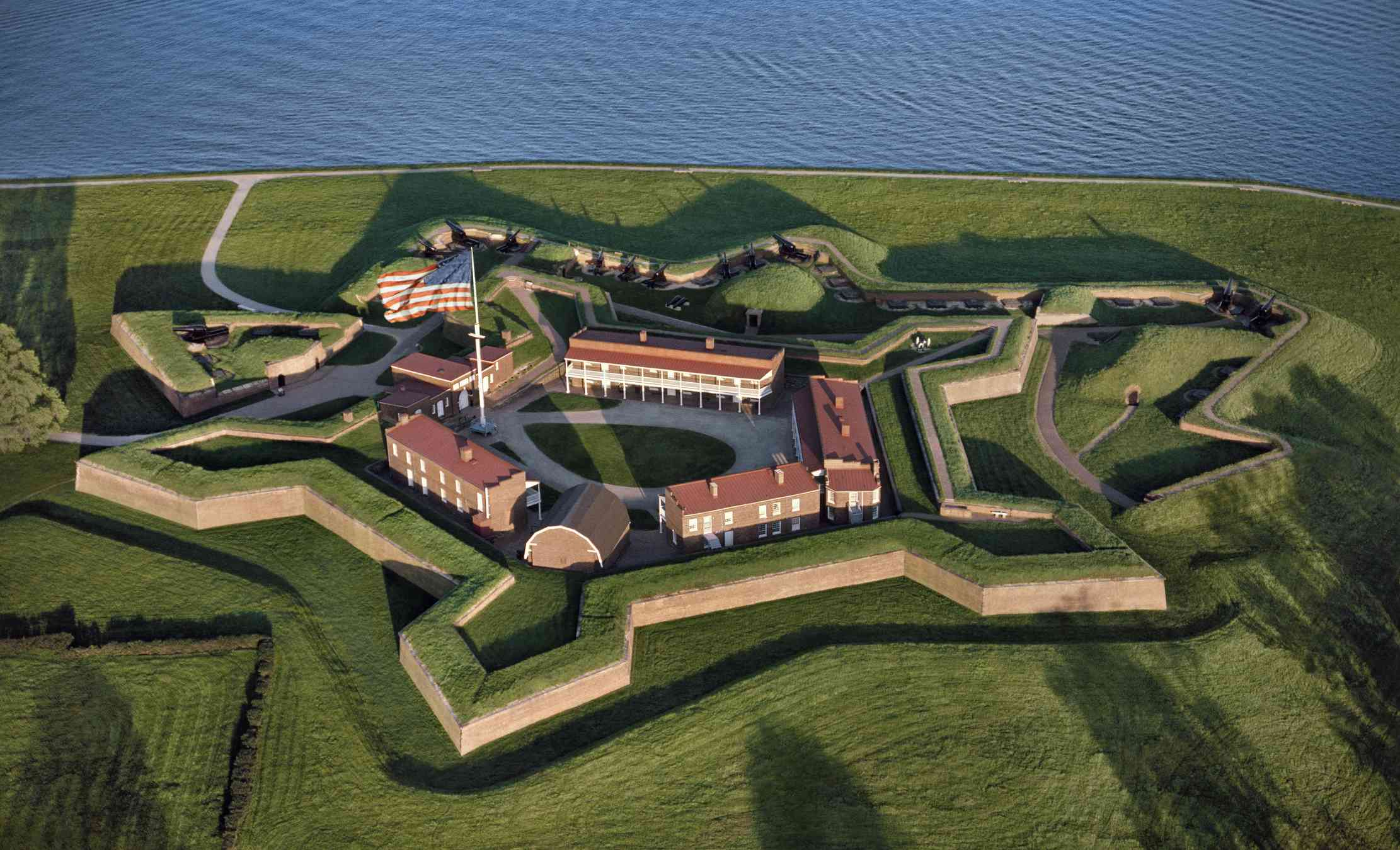arial view of pentagonal-shaped Fort McHenry National Monument and Historic Shrine surrounded by manicured green lawns and adjacent to the Patapsco River