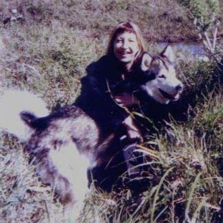 Woman hugging malamute dog in field