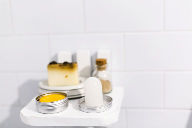 Crystal deodorant on shelf in a white bathroom with soap and salts.
