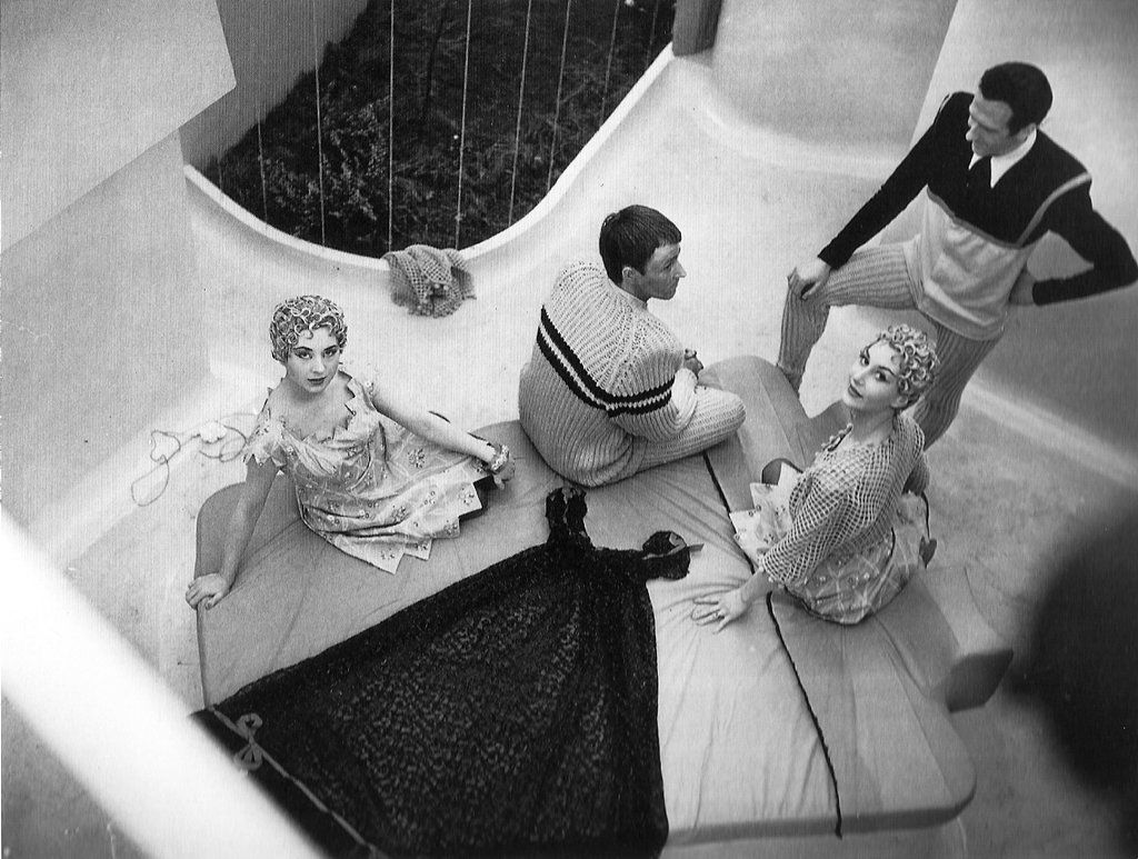Overhead view of three people perched on a fold-down bed, with another man standing nearby