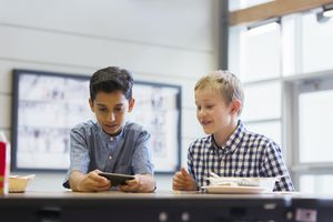 Two boys looking at a cellphone in a school cafeteria