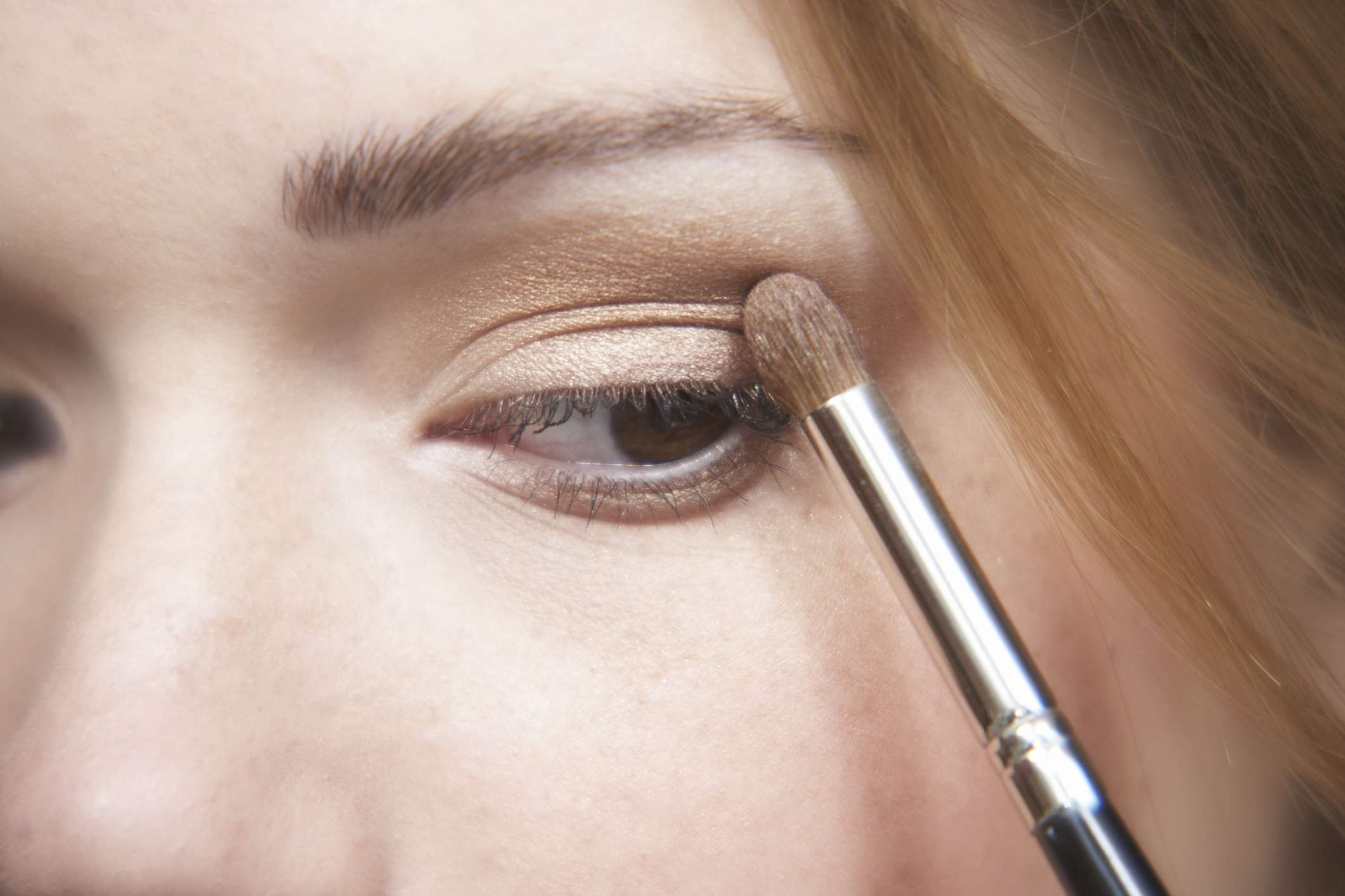 A woman applies eyeshadow on her eyelid with a brush.