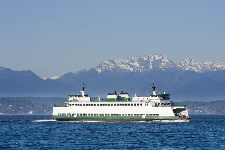 A Washington State Ferries boat passes by mountains on a clear day