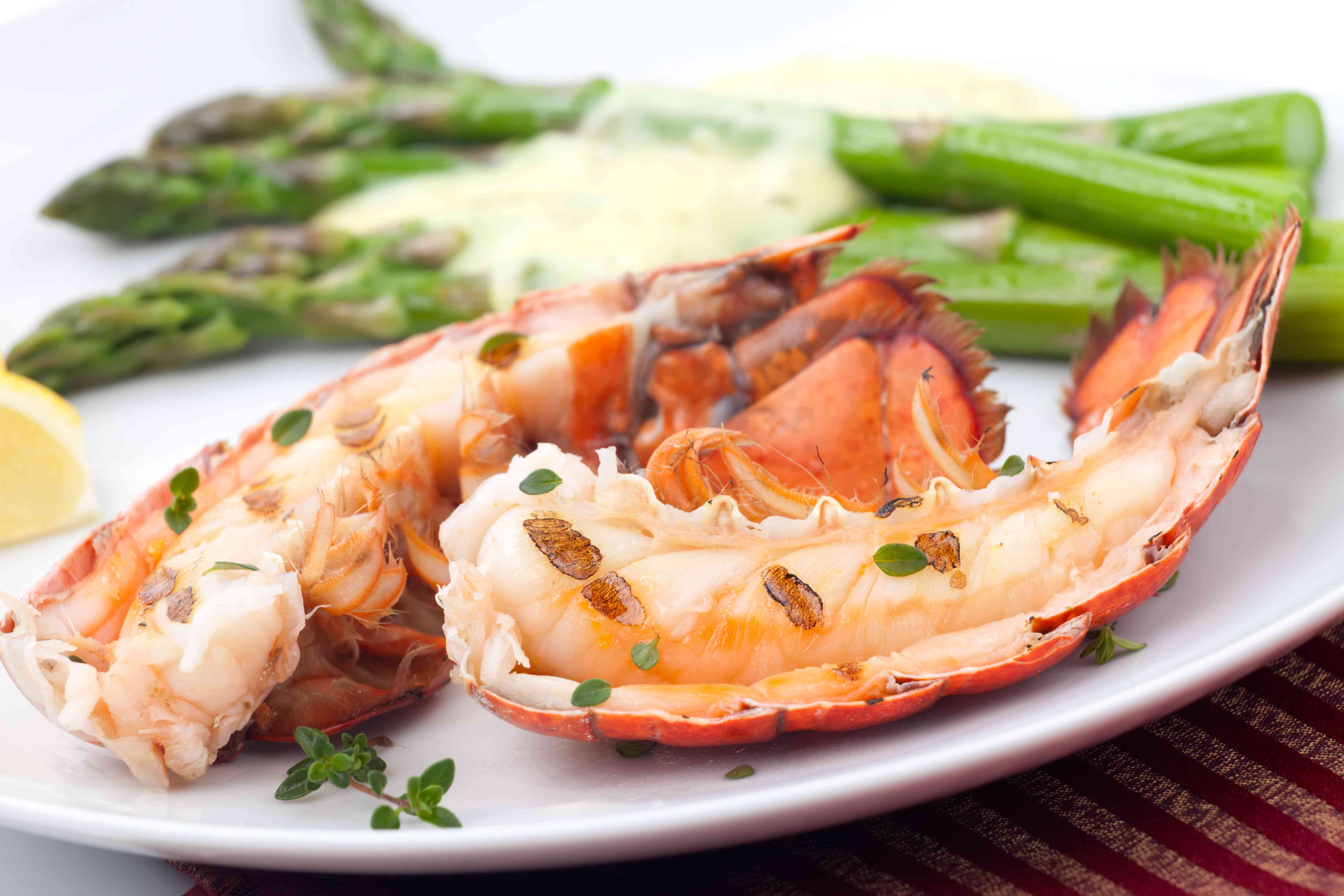 Lobster tail halves on a plate with asparagus