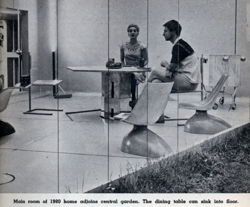 A man and woman sit at an angular table in a courtyard