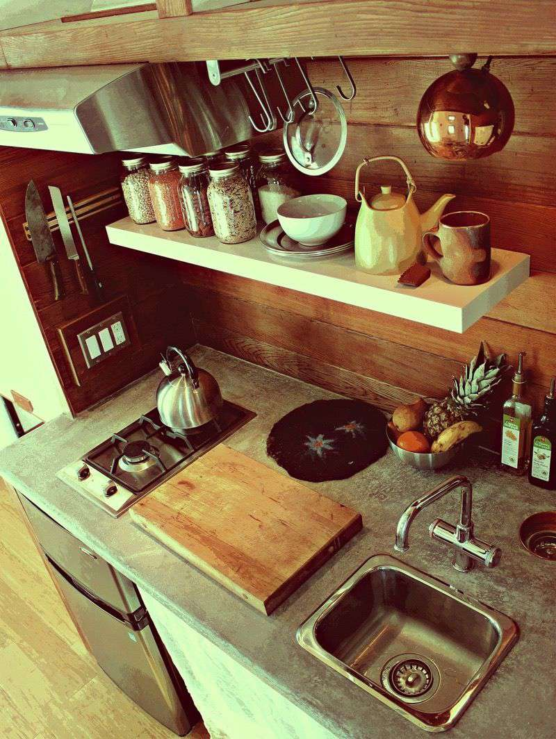 Small kitchen with a sink, counter, and spice rack visible