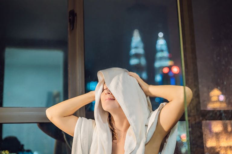 woman drying her hair with white towel after a shower at night with city lights in the background