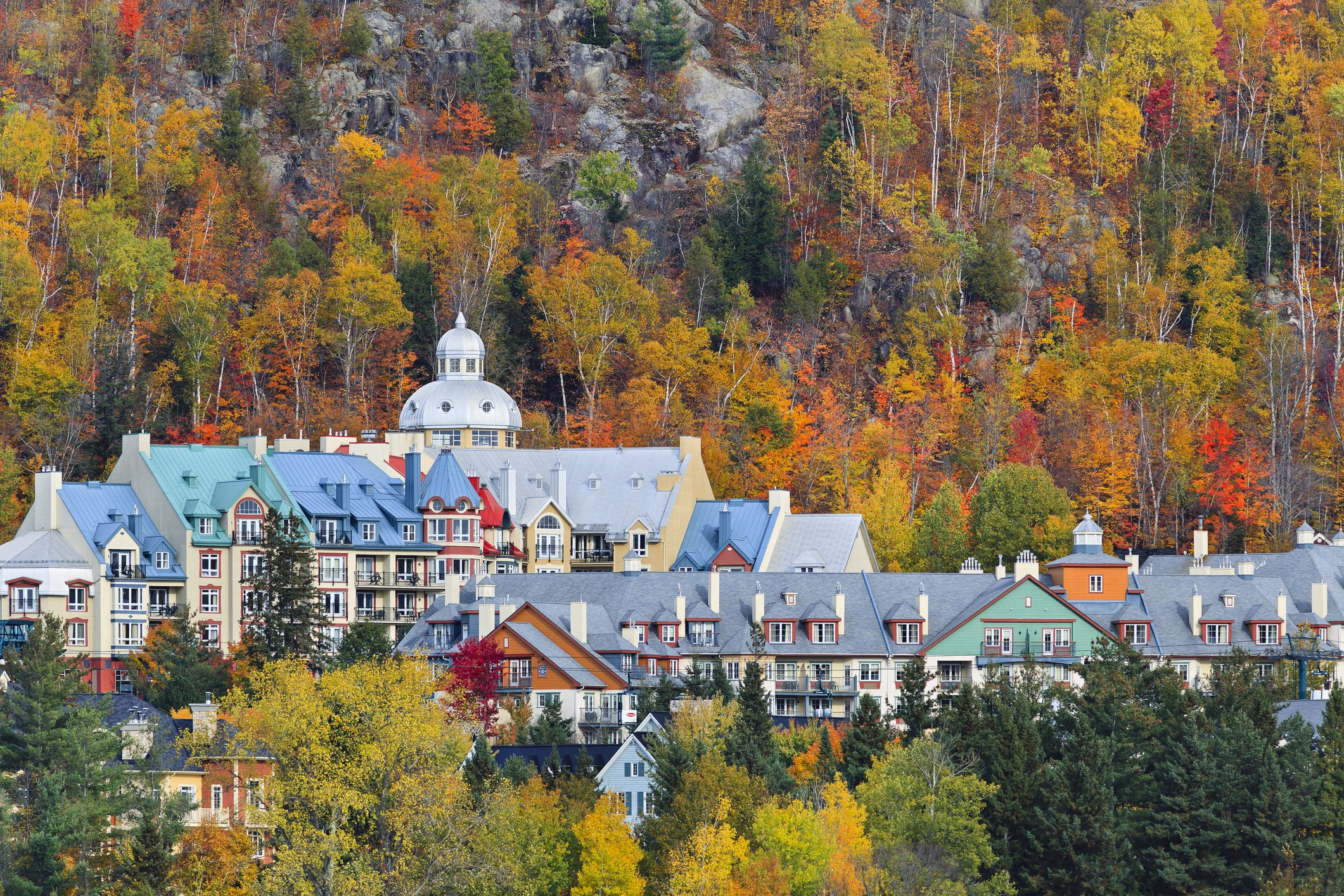 Mont Tremblant Village, a small village with blue, red, and green roofs set in a dense forest of trees in shades of orange, red, gold, yellow, and green