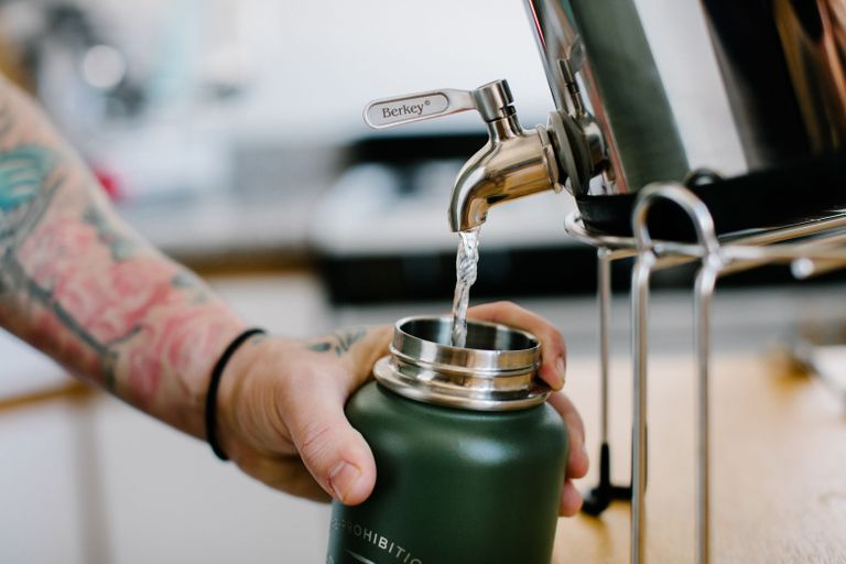 tattooed arm and hand fill up reusable canteen at water station