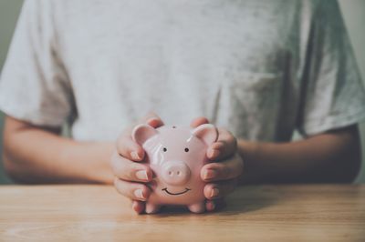 Man hand holding piggy bank on wood table. Save money and financial investment