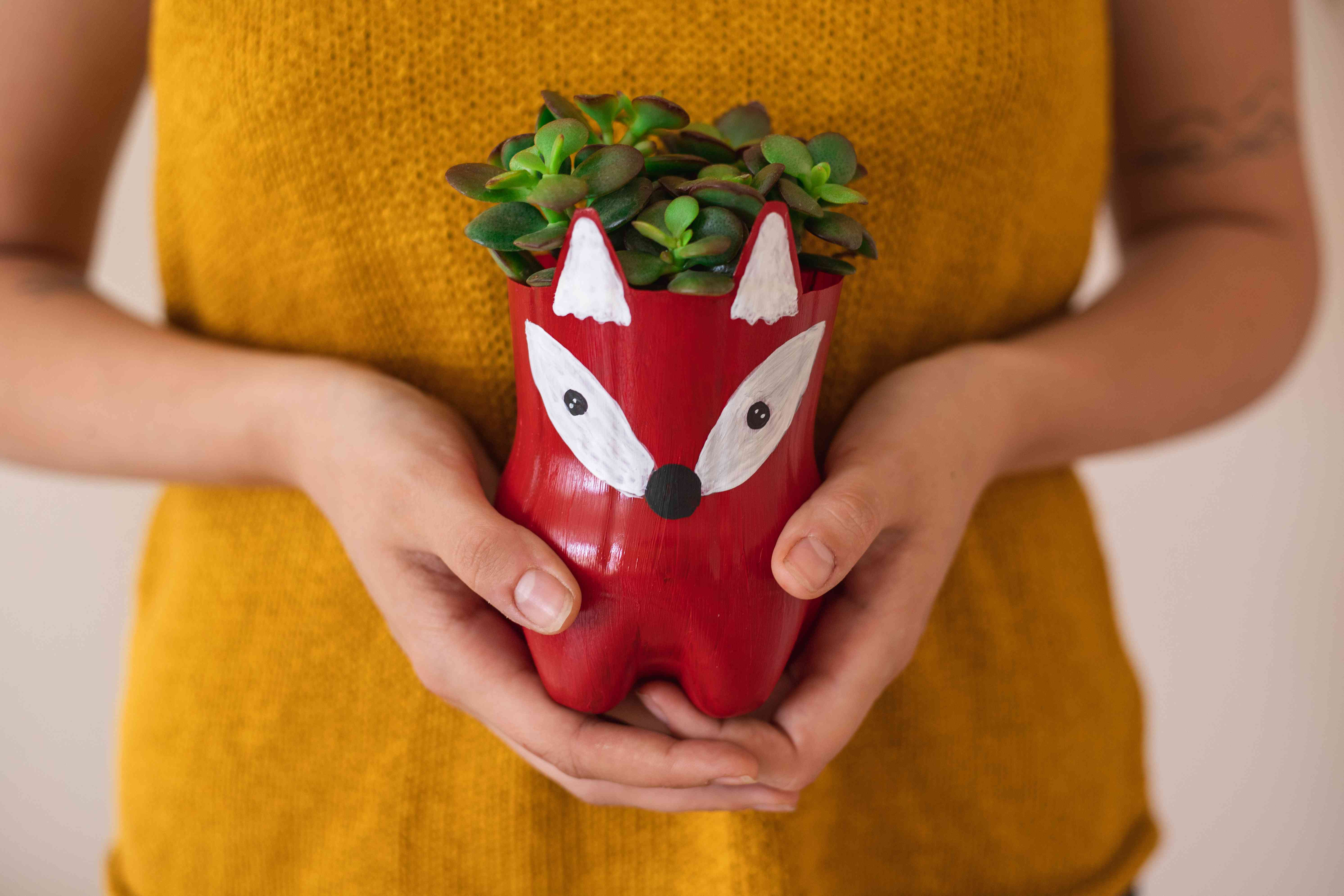 a plastic bottle has been painted and upcycled into a plant pot held by person in mustard shirt