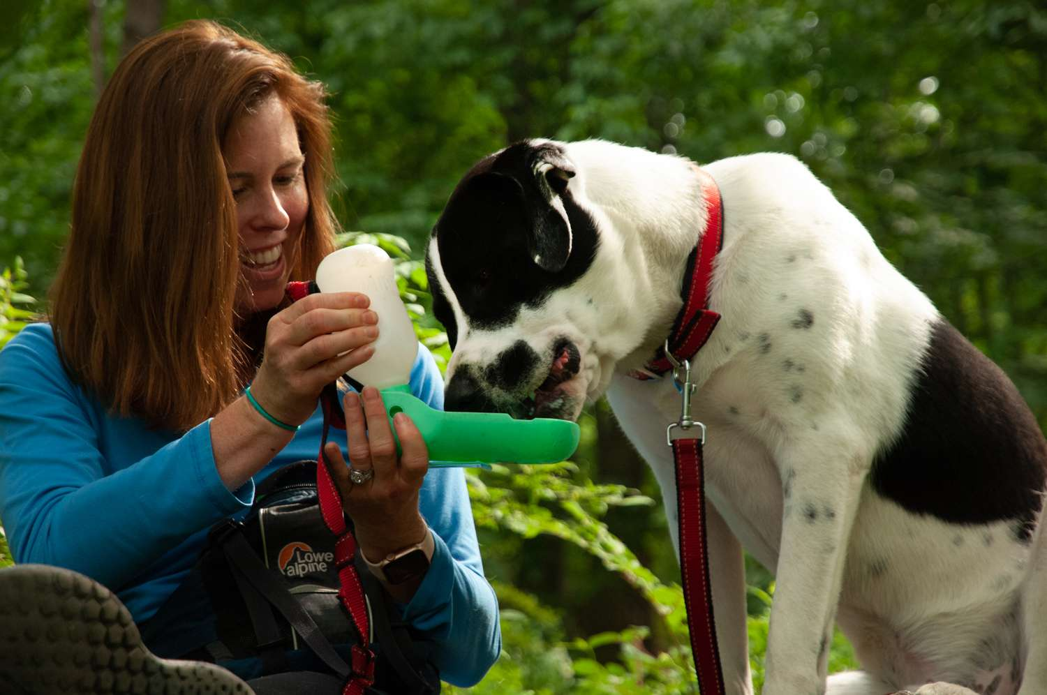 red-headed woman smiles as dog drinks out of portable water carrier on hike