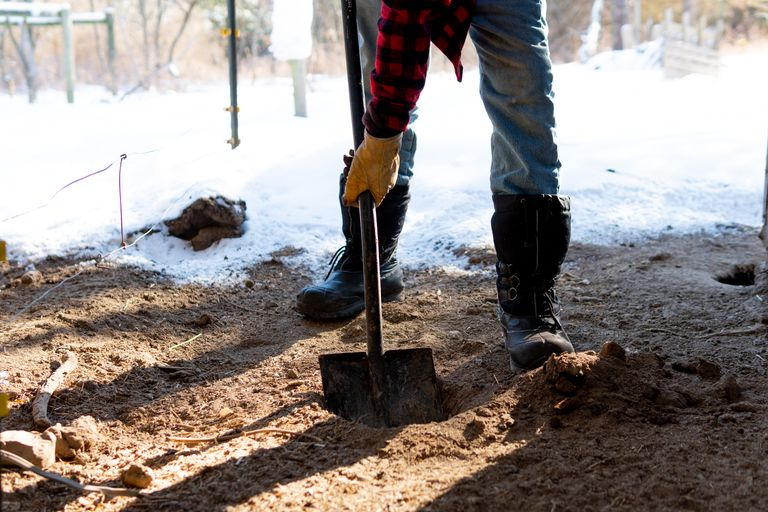 guy in boots shovels snow and dirt in winter garden