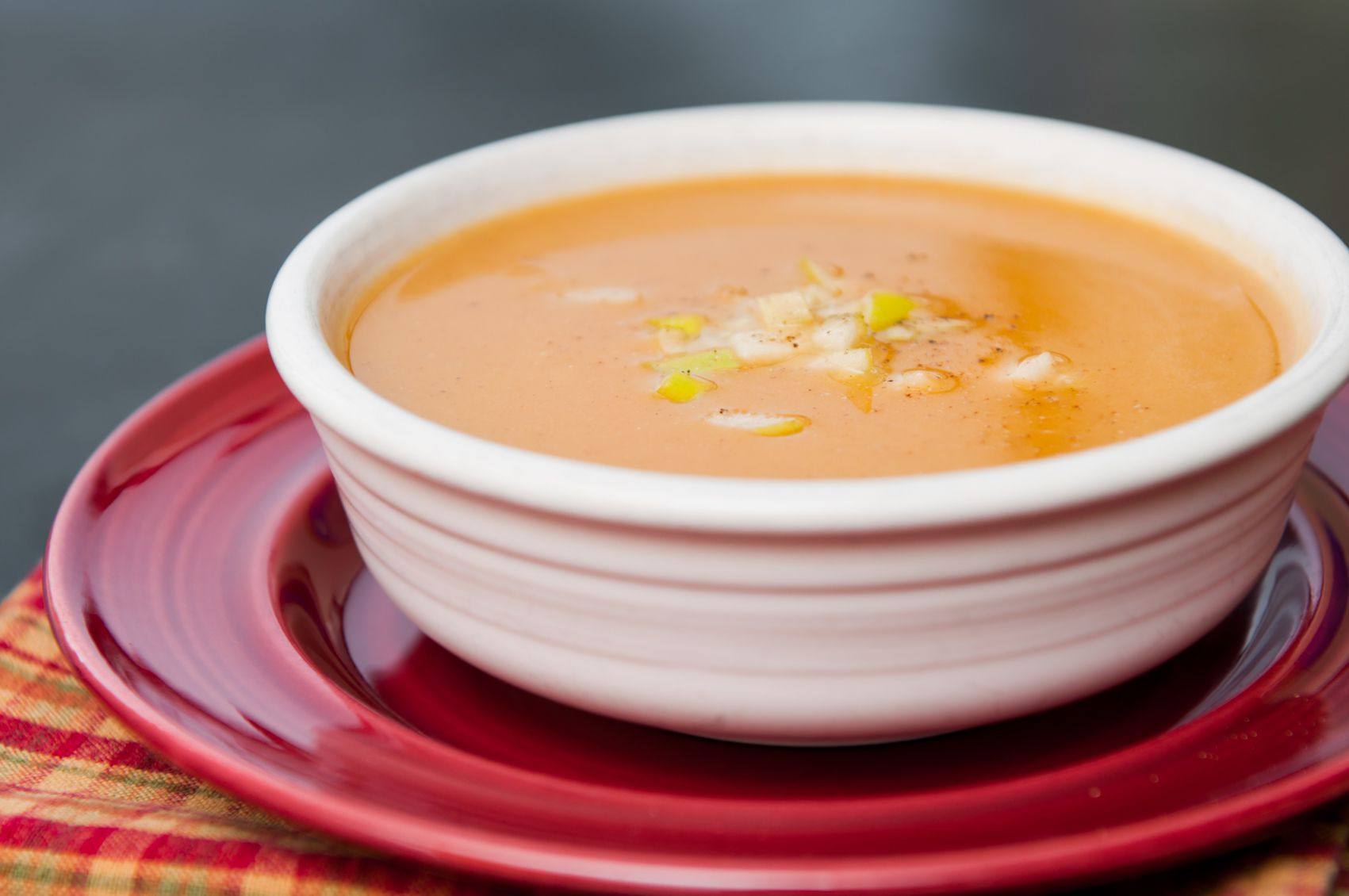 A bowl full of butternut squash soup topped with diced apples and pepper
