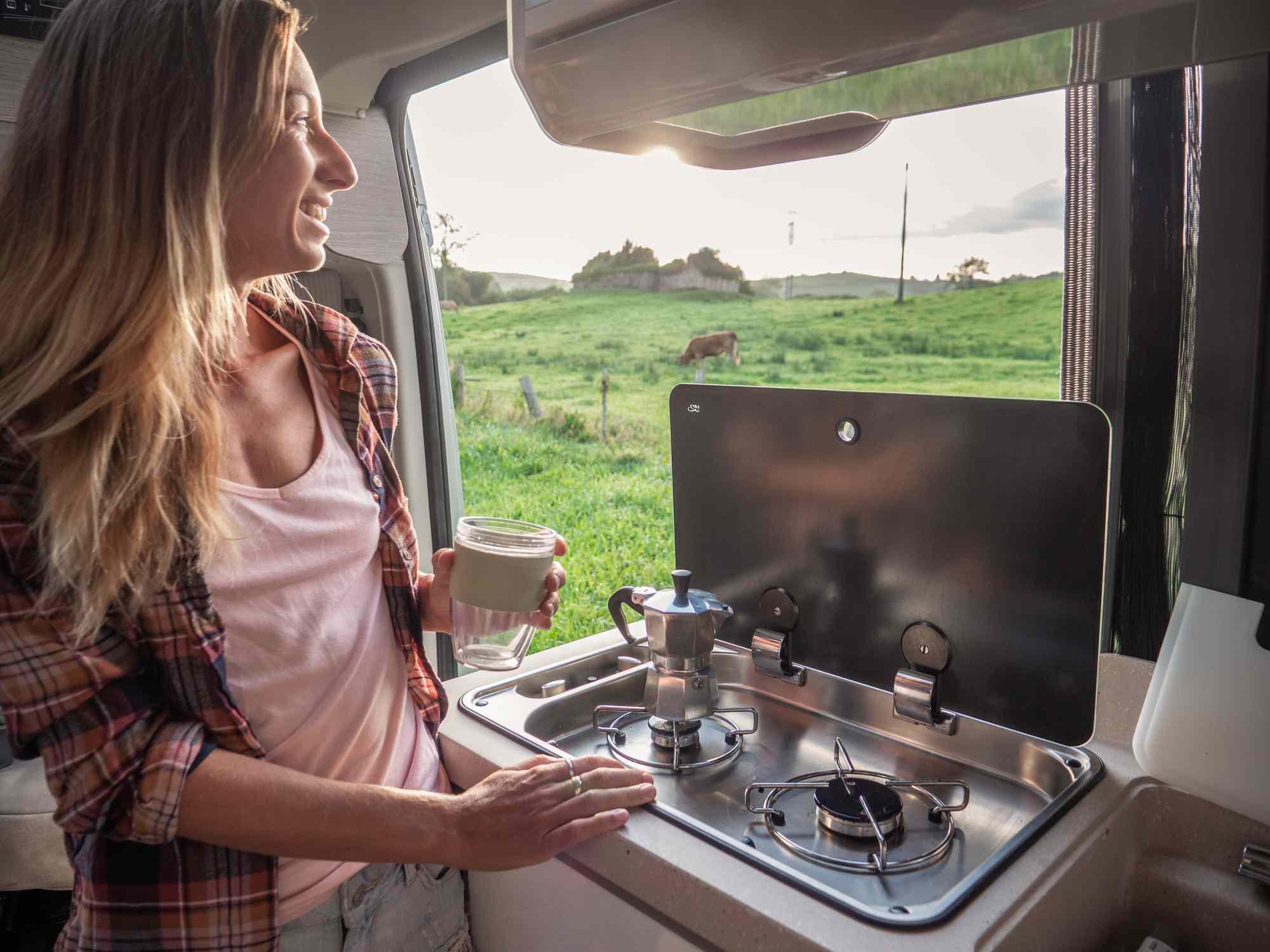 Person making coffee in motorhome with door open
