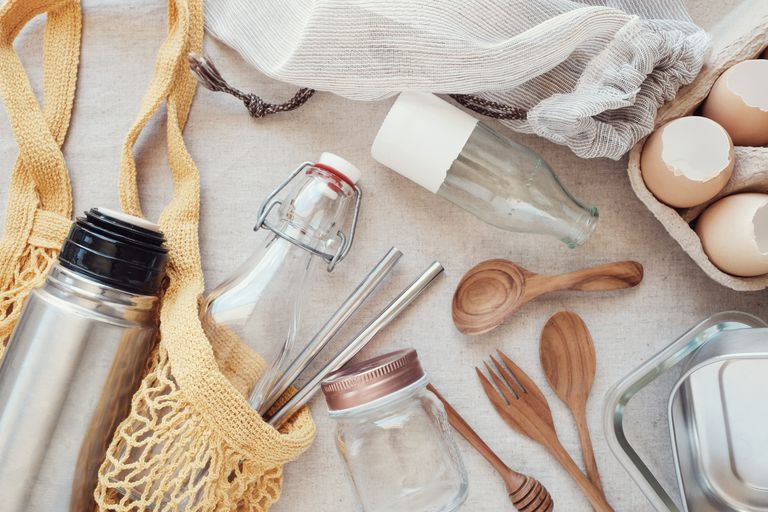 Glass bottles, wooden utensils, cloth shopping bag on table surface