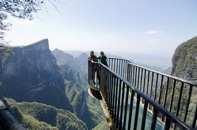 Two people standing at the end of an overlook with mountains in the background