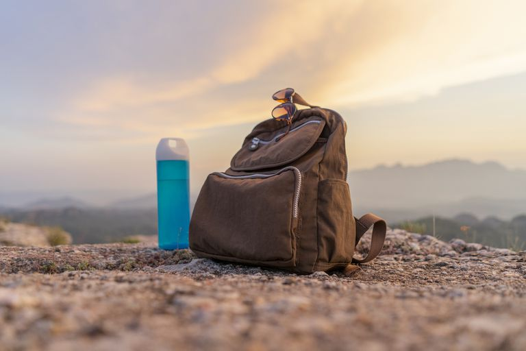 Water bottle and backpack sitting on rocky ground
