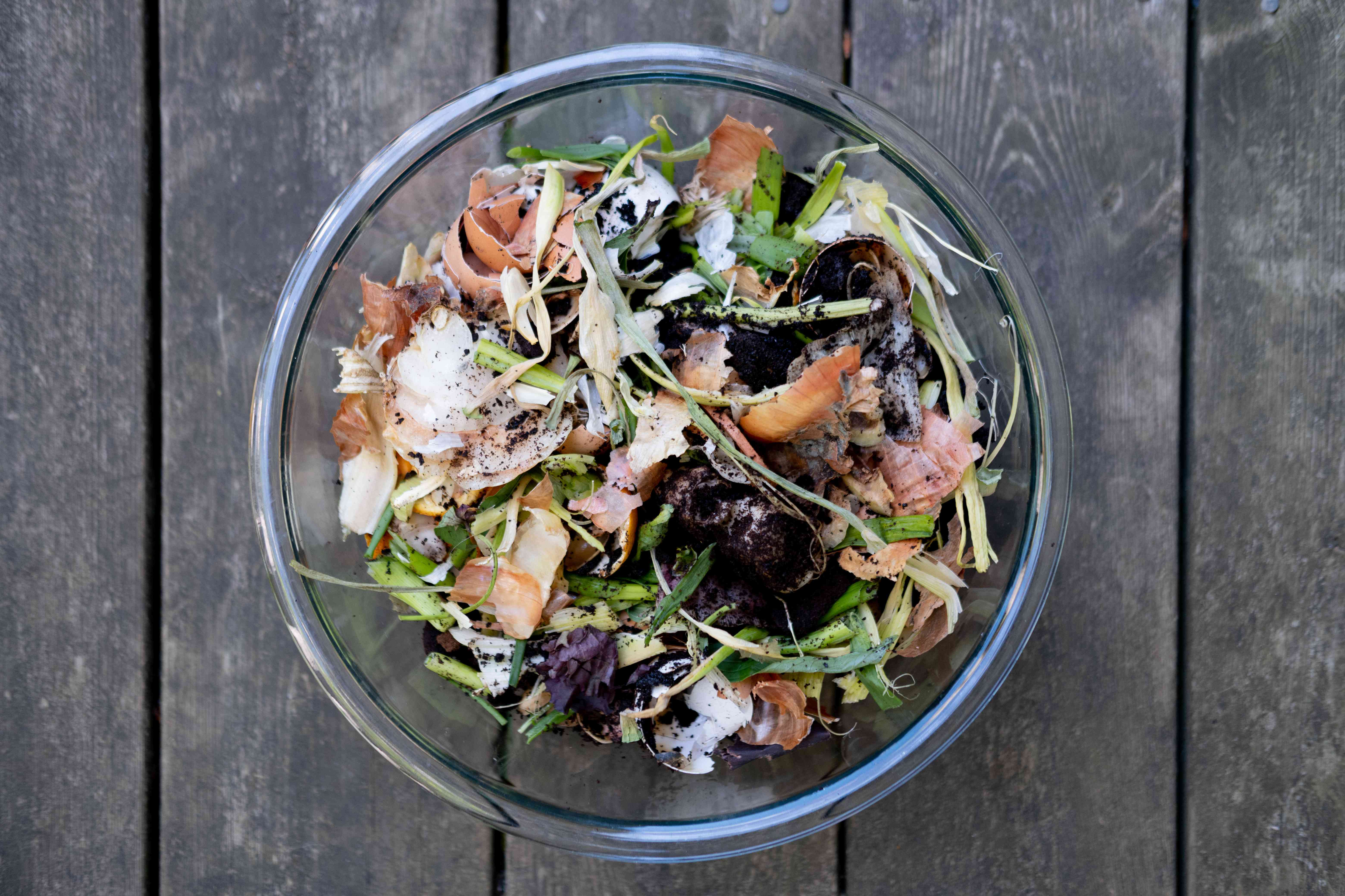 overhead view of clear glass bowl holding food scraps and egg shells