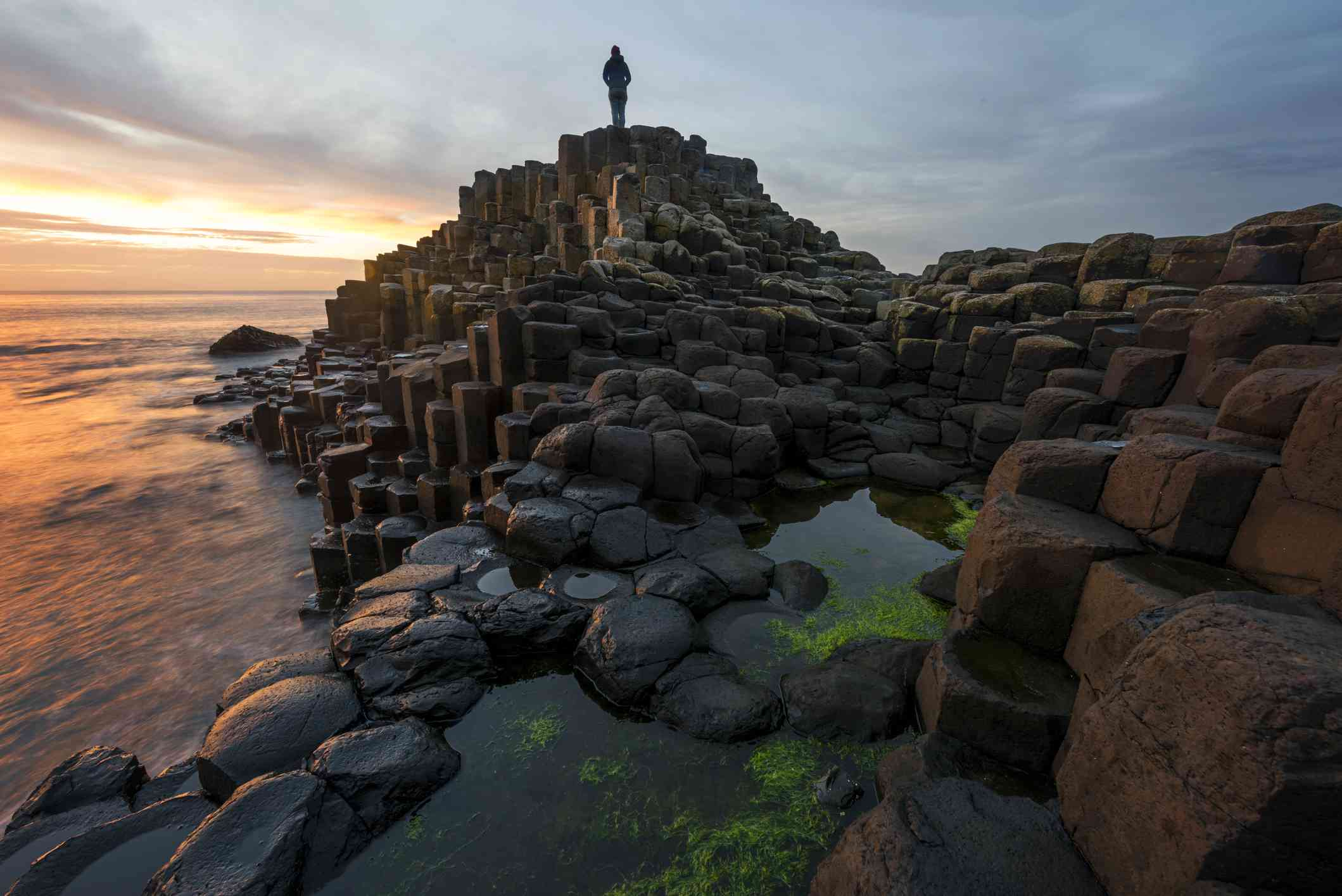 woman standing on Giants Causeway in Northern Ireland at sunset