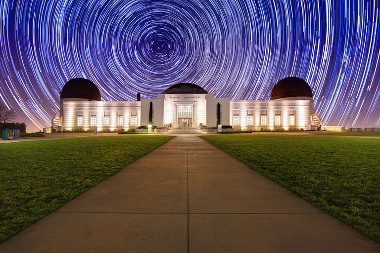 Star trails in the sky above a white building