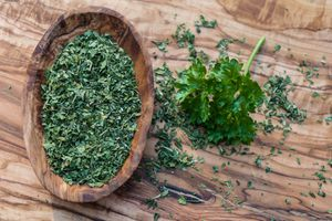 Wooden surface with a sprig of fresh curly parsley next to a wooden bowl of dried parsley