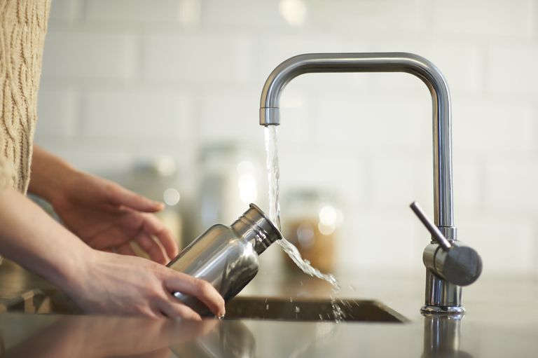 Woman filling a metal water bottle at the sink
