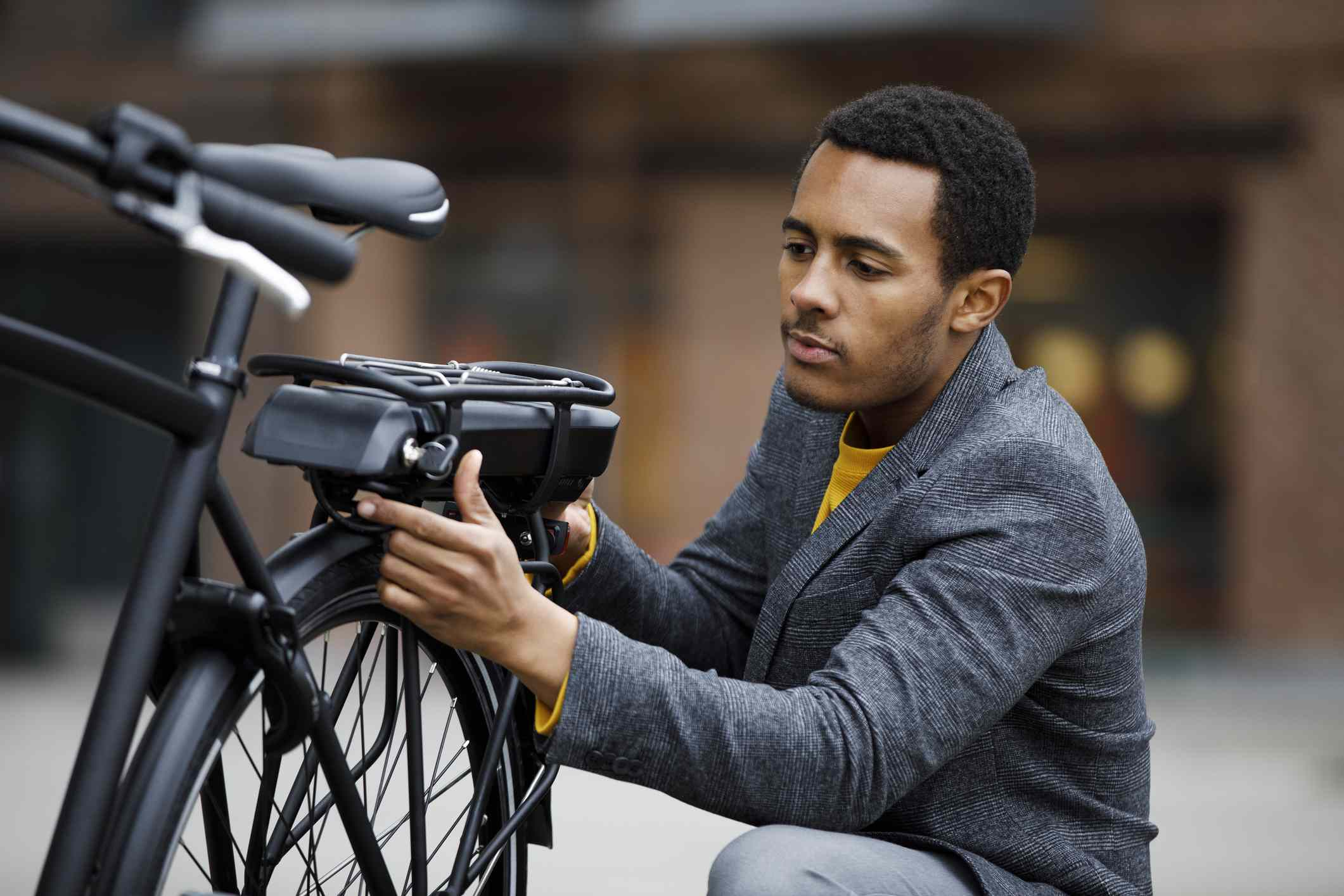 Young man changing battery pack on electric bicycle