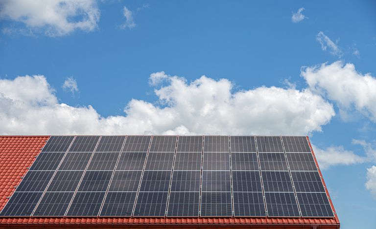 The roof of the house with solar panels against the sky.