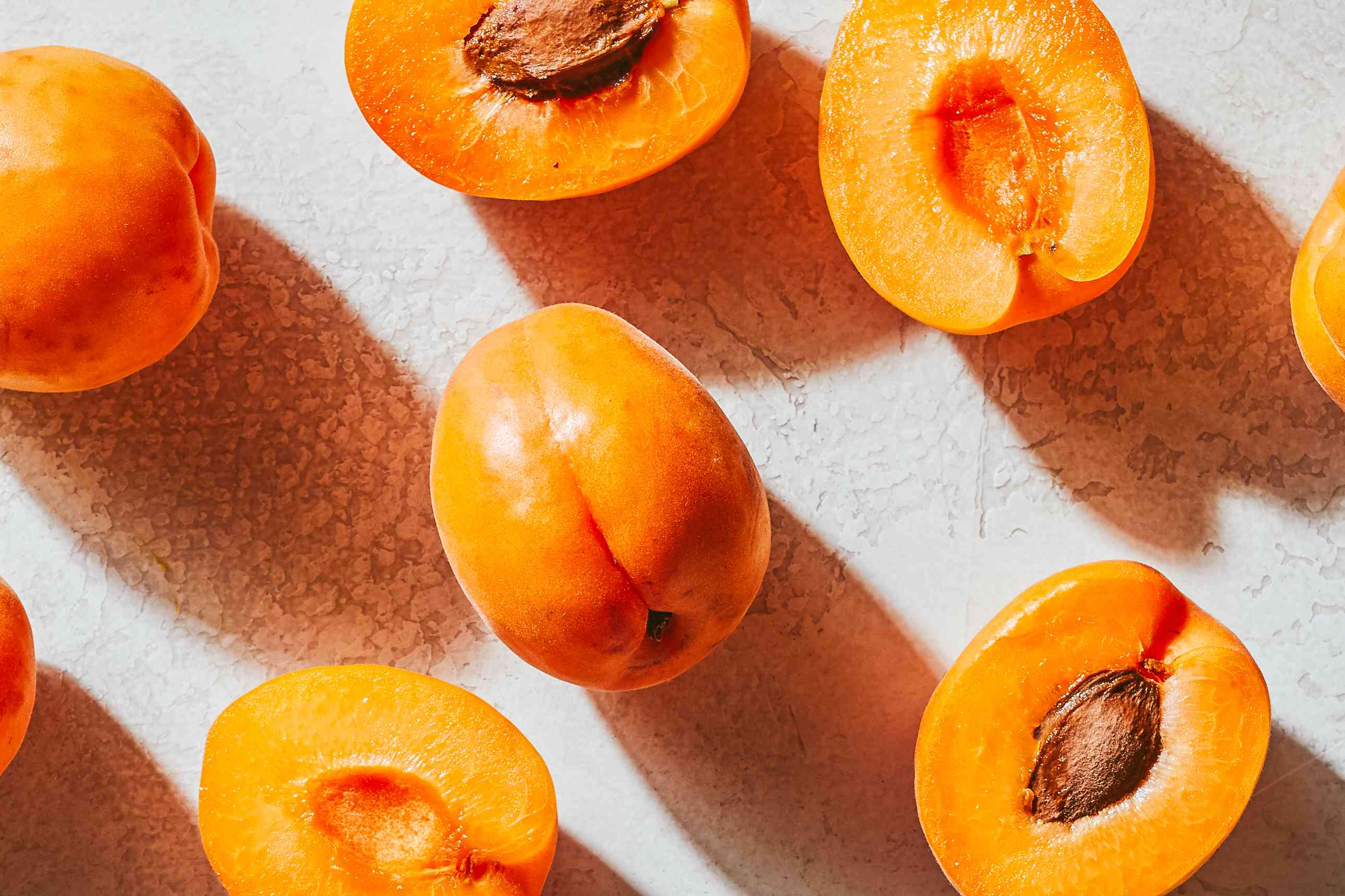 ripe apricots cut to show stone scattered on textured white surface