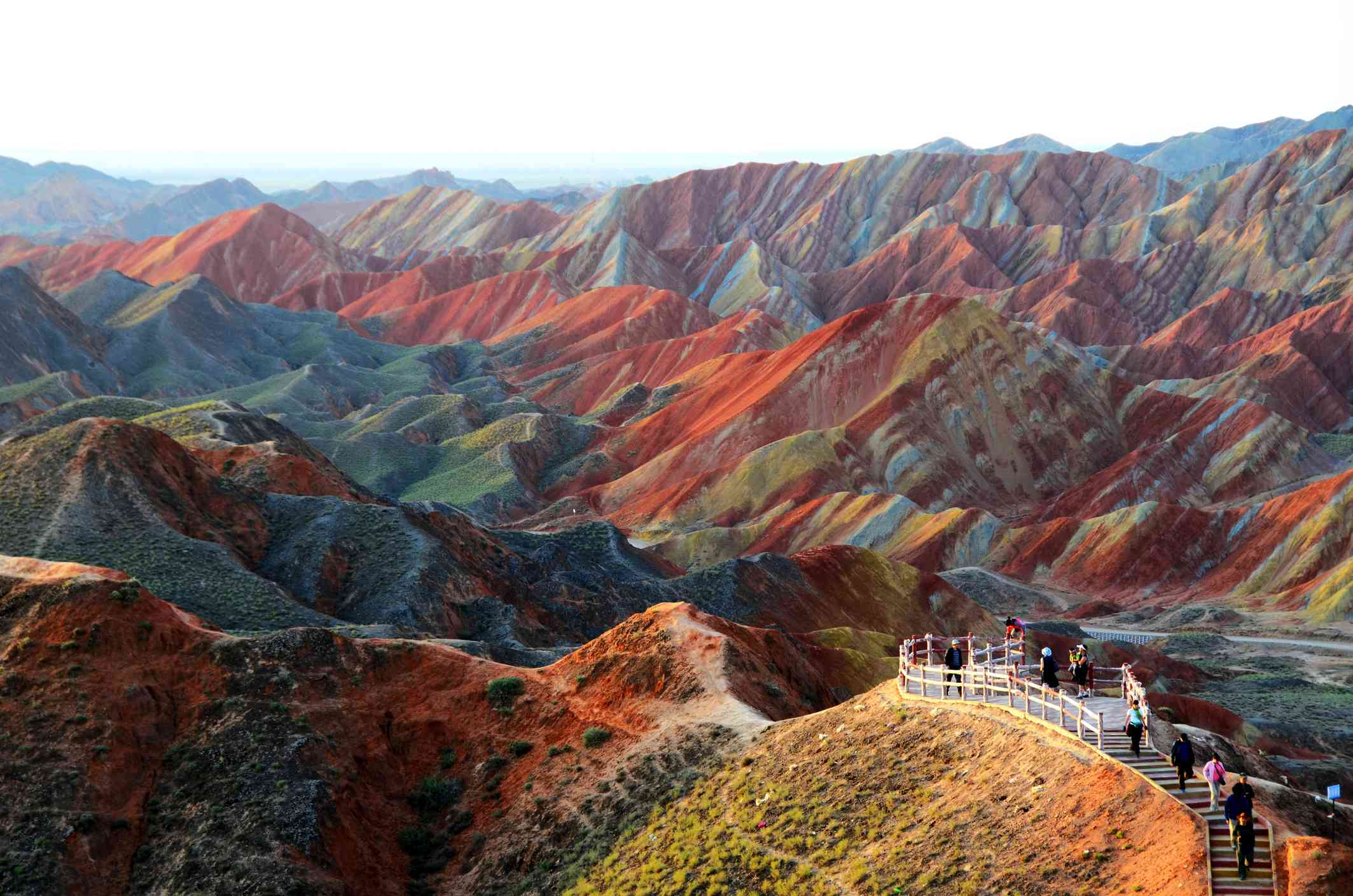 Tourists on a trail look out over a landscape of striped red, blue, and yellow mountains
