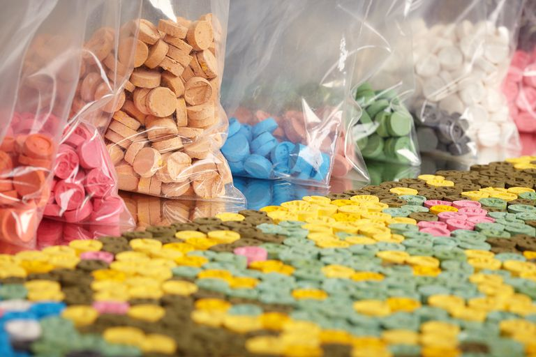 Colorful MDMA pills in bags and spread out on a table