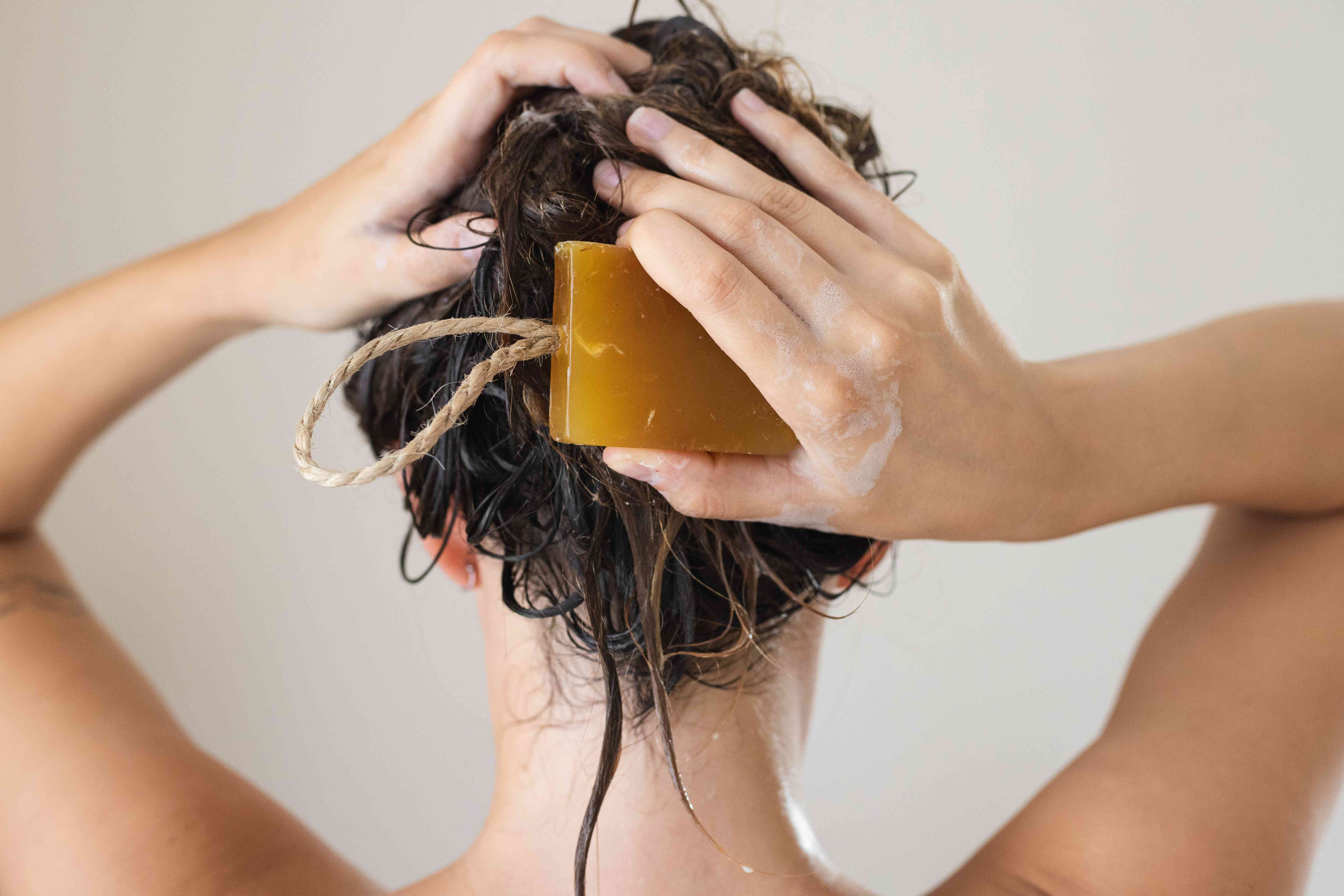 back of woman's head washing her hair with brown shampoo bar