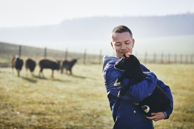 Young farmer holding lamb against pasture with herd of sheep