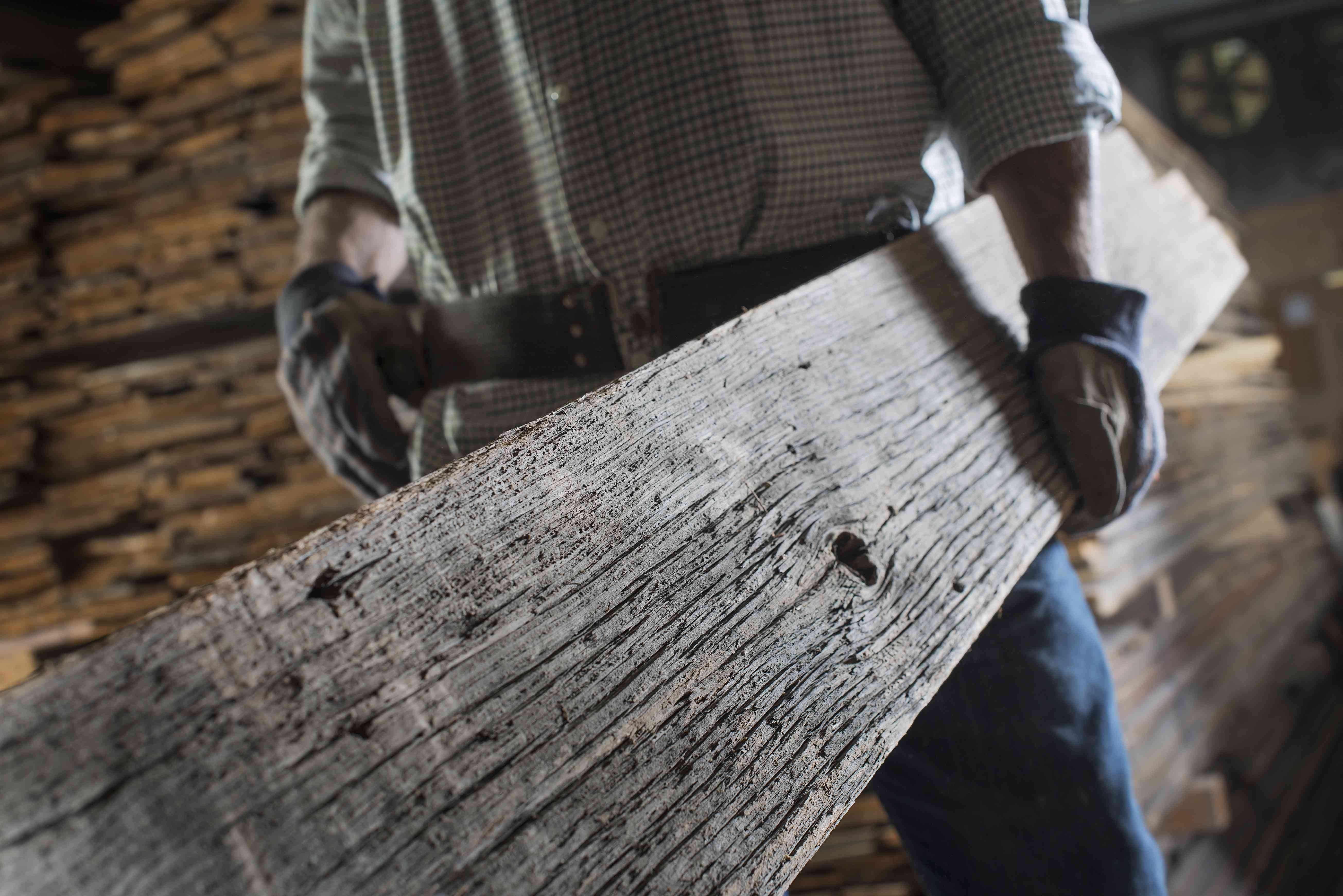 A man carrying a large plank of reclaimed wood