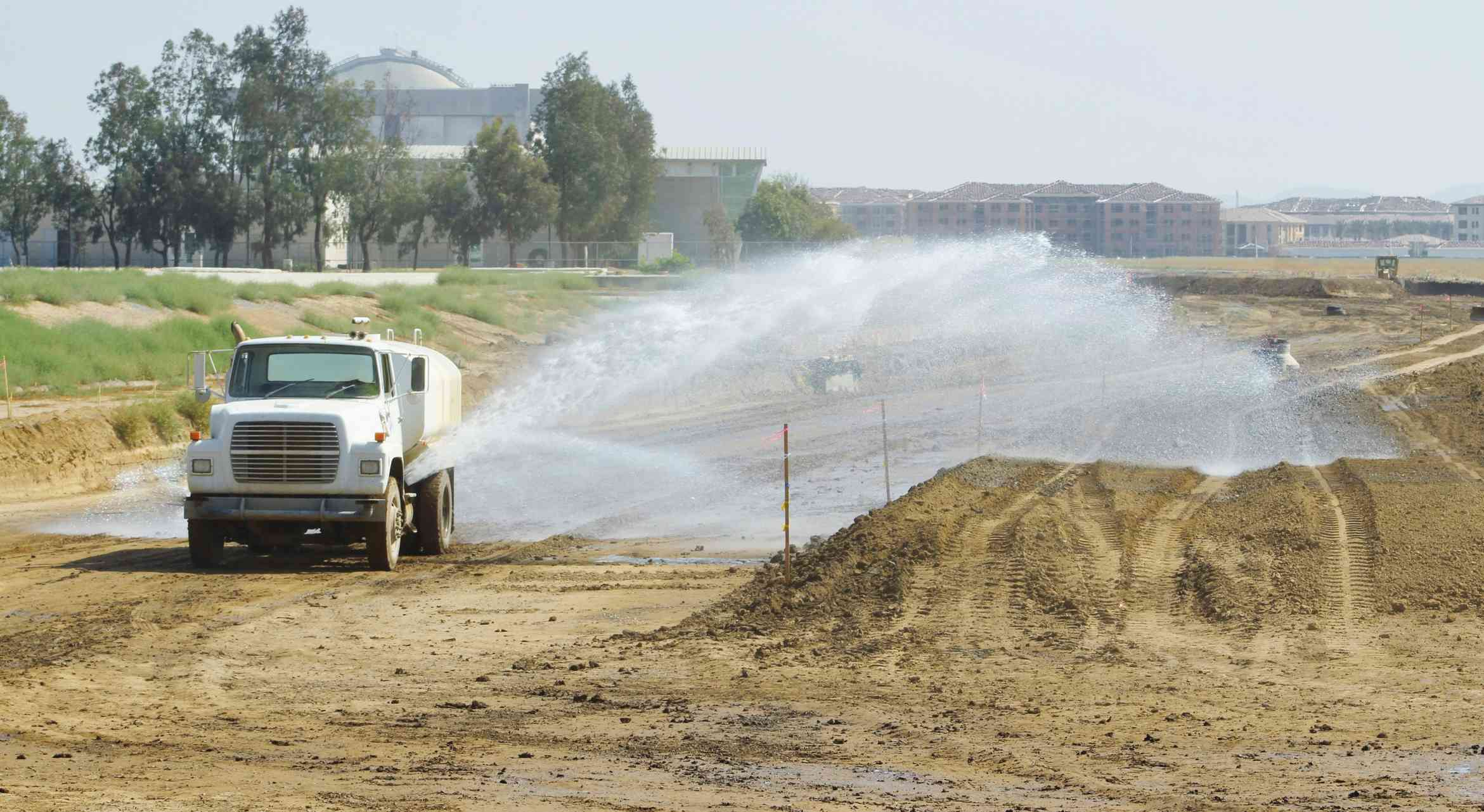 A truck spraying water onto dirt on a construction site.