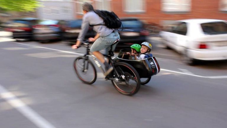A man riding a bike with a sidecar with two small children inside wearing helmets