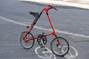 A red Strida bike parked in a bike lane.