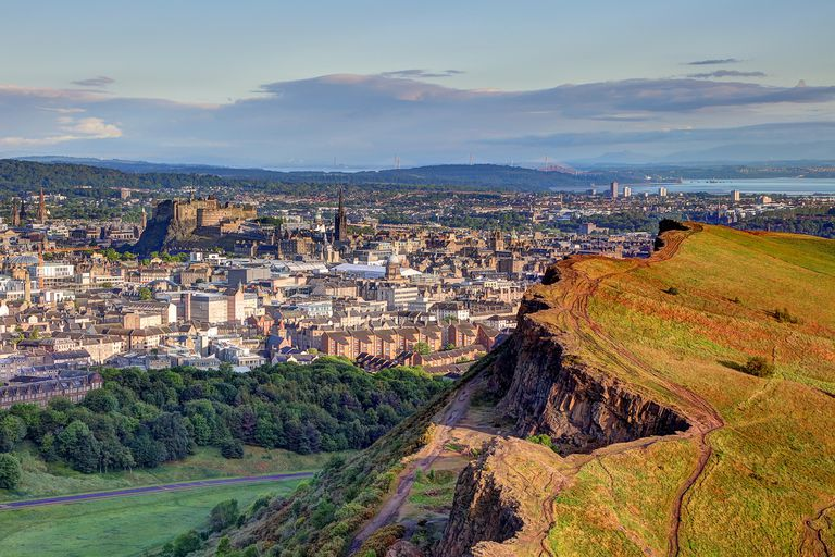 View of Edinburgh old town and castle with part of Arthur's Seat mountain visible in foreground, green grass and lush trees below, and blue sky above.