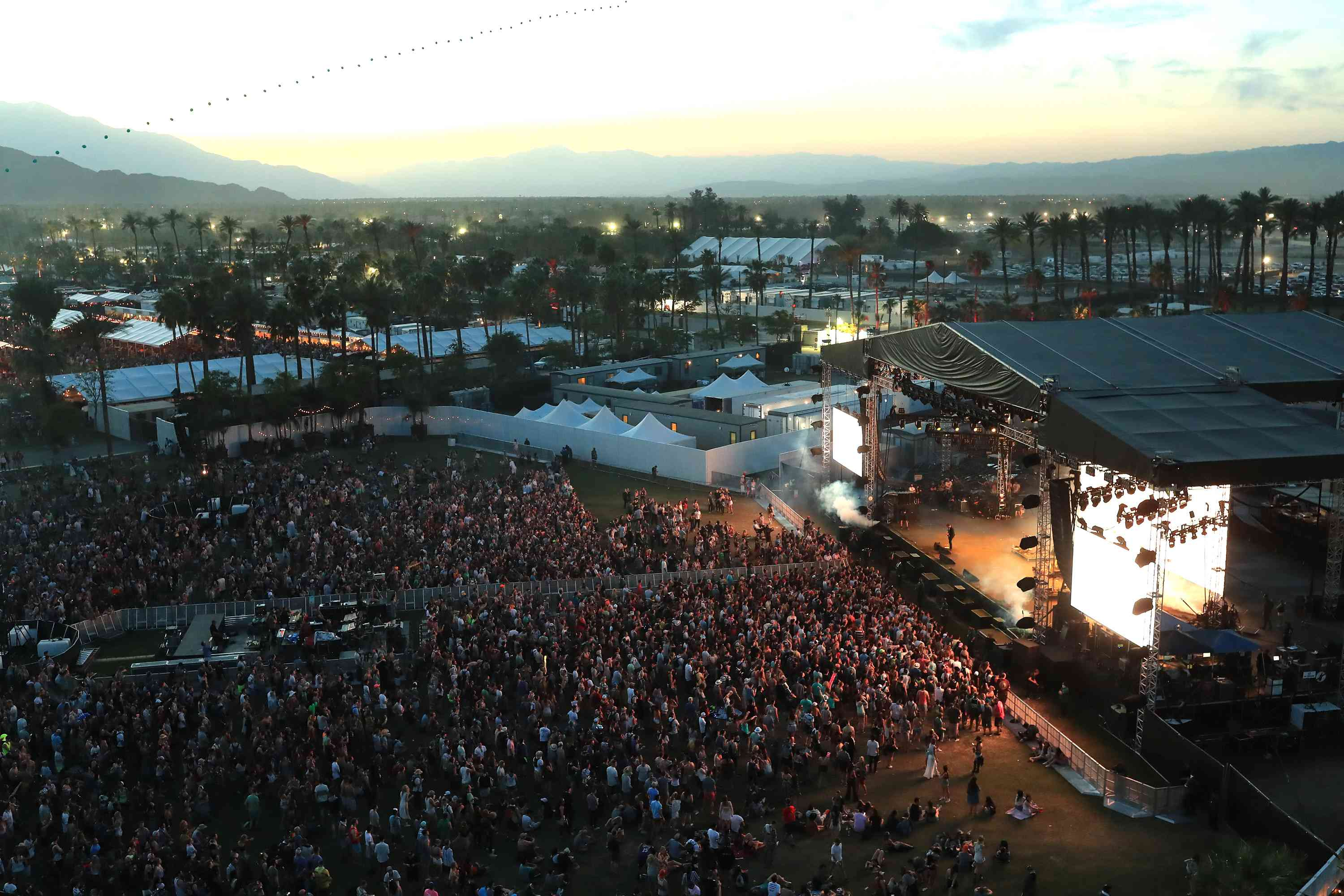 Aerial view of sunset over Coachella Music and Art Fesetival with a crowd of people facing toward a lit stage with palm trees and mountains in the distance