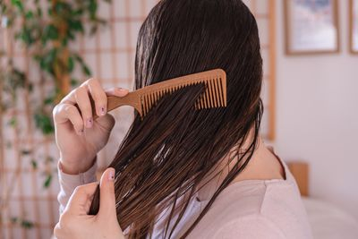side profile shot of woman combing wet brown hair with brown comb