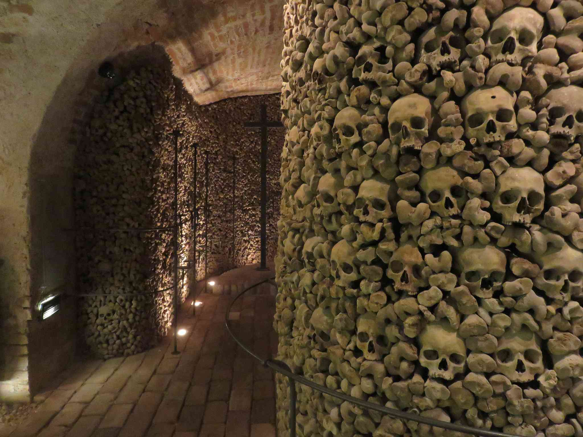 A wall made of human skulls and bones along a hallway in Brno Ossuary