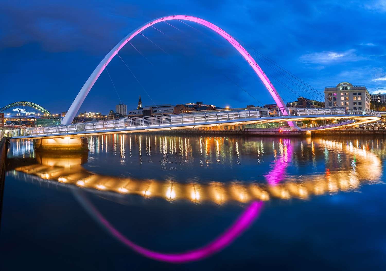 The Gateshead Millennium Bridge is illuminated in pink at dusk