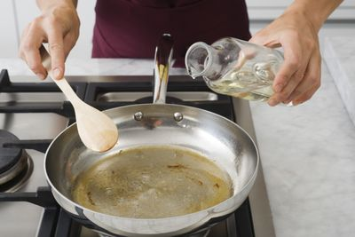 Person pouring oil into a frying pan on the stove