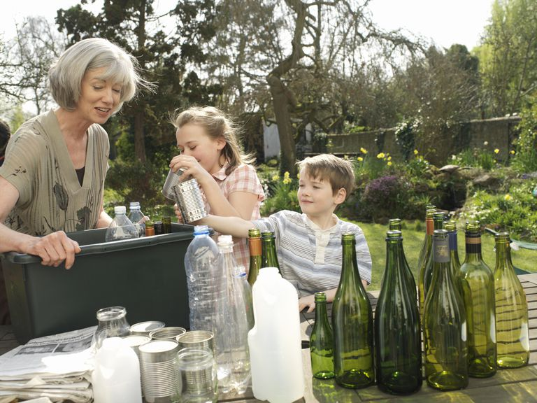 A family loading recyclables into a bin by a garden.