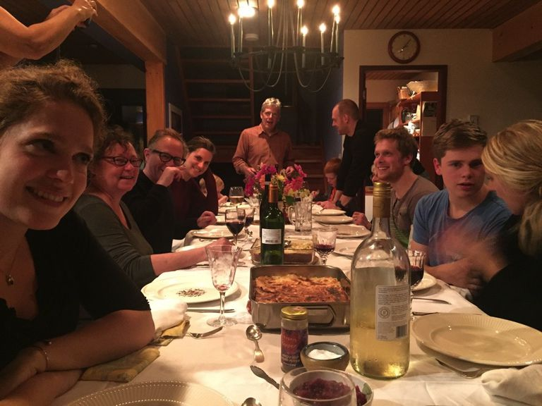 a large group of people seated at long table for thanksgiving dinner