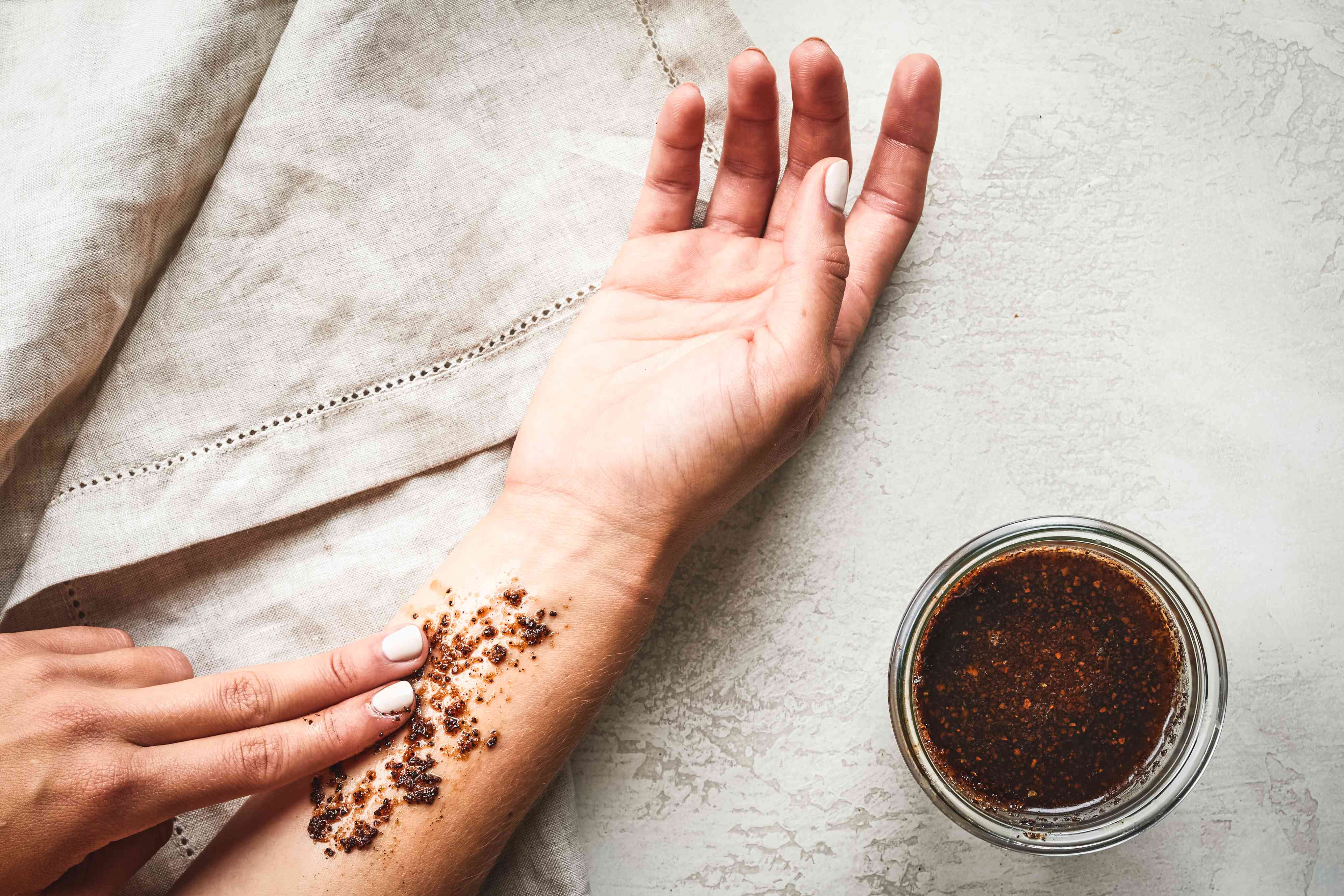 hands rub homemade coffee grounds-coconut oil on outstretched forearm