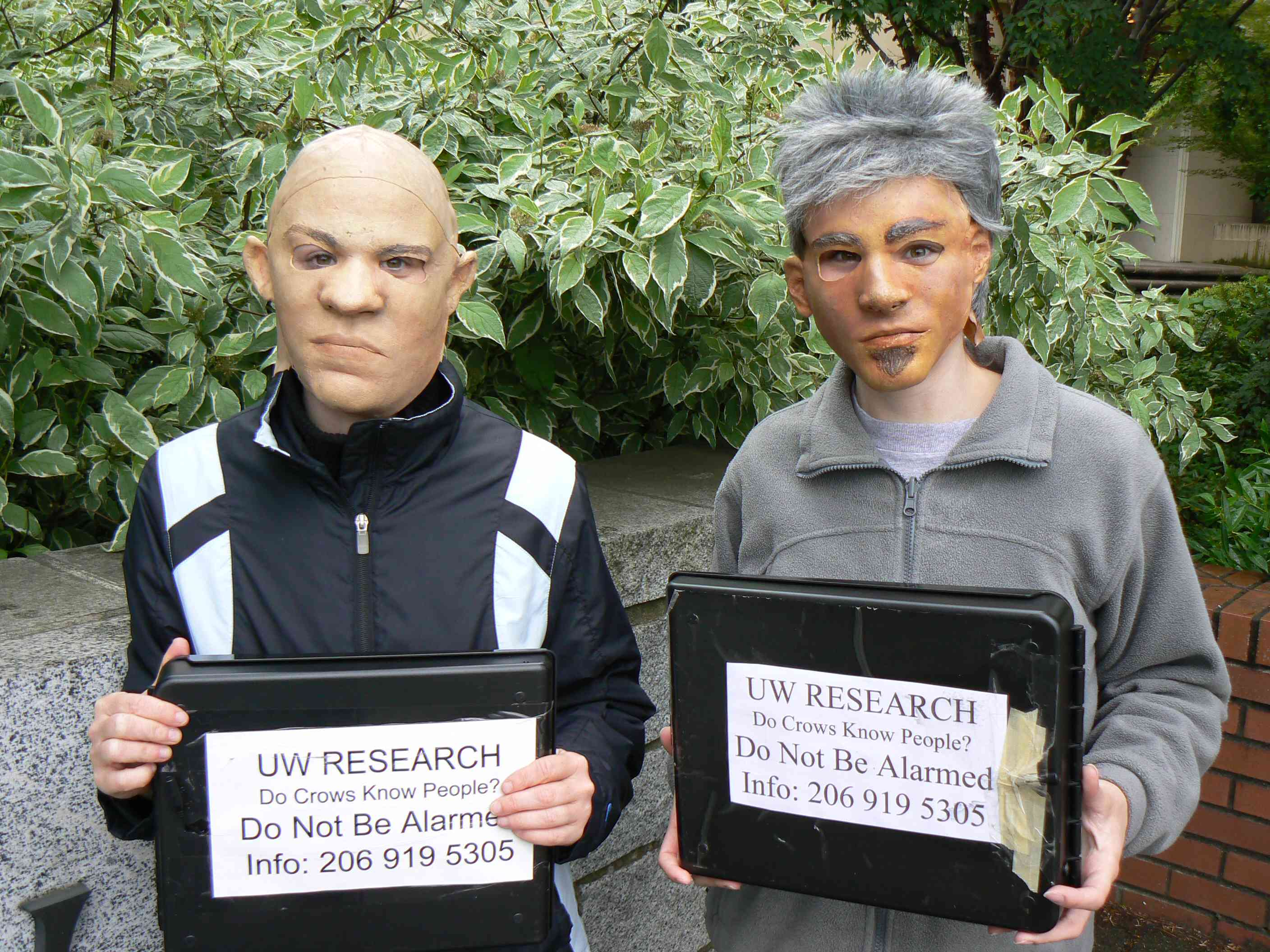 crow researchers wearing masks and holding signs