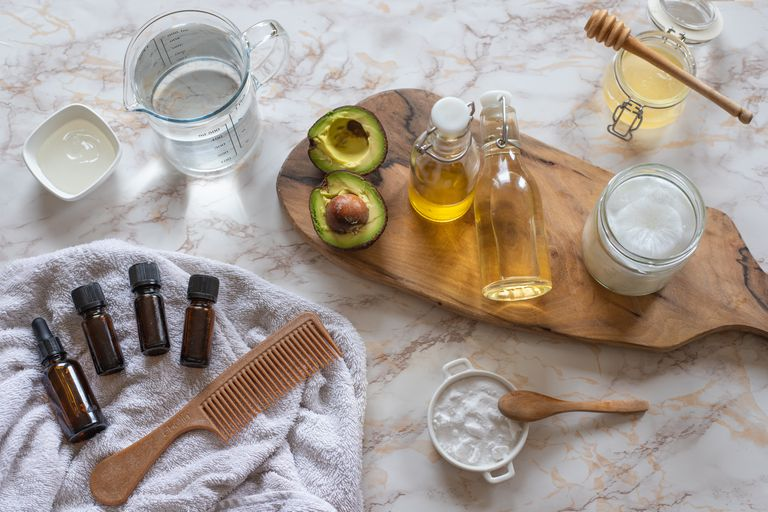 flat lay product shot of natural hair care: essential oils, apple cider vinegar, avocado, baking soda, coconut oil
