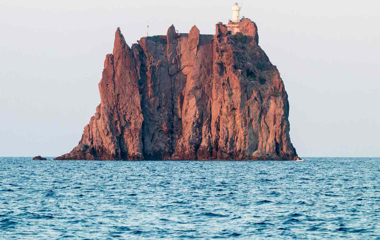 Strombolicchio Lighthouse sits atop a giant sea stack in the Aeolian Islands of Italy